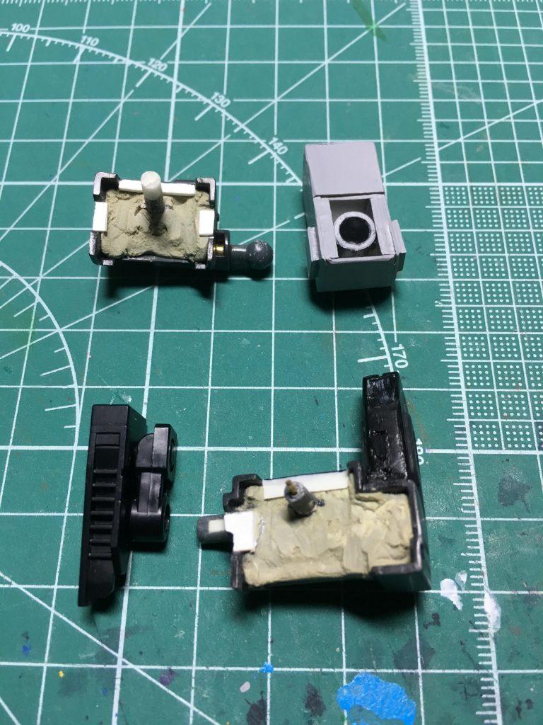 ソード・ランチャーの基部はBB戦士のスカイグラスパーとのセットから流用。裏側をエポキシパテで埋め、背中との隙間を0.3mmプラ板で埋めます。    軸は0.5mmシンチュウ線を仕込みながら約2mm延長しました。    接続軸はジャンクパーツの中から見繕っています。ランチャーは股関節のボールジョイント、ソードは腰軸(5mm径)を使用。ソードの軸はそのままでは回転させるとねじ切れてしまうので、紙ヤスリで削ってクリアランスを調節。   いずれも1.5mmシンチュウ線を通しながら接着。プラセメントでがっちり固定します。ソードのマウントは塗膜との干渉を避けるため内側を削っています。